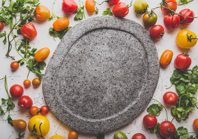 Серая пустая каменная плита и свежие варя ингридиенты - зеленый цвет красные, желтые оранжевые томаты и травы Изображения космоса стоковая фотография