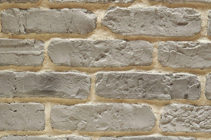 Серая стена кирпичей с бежевым цементом стоковое фото
