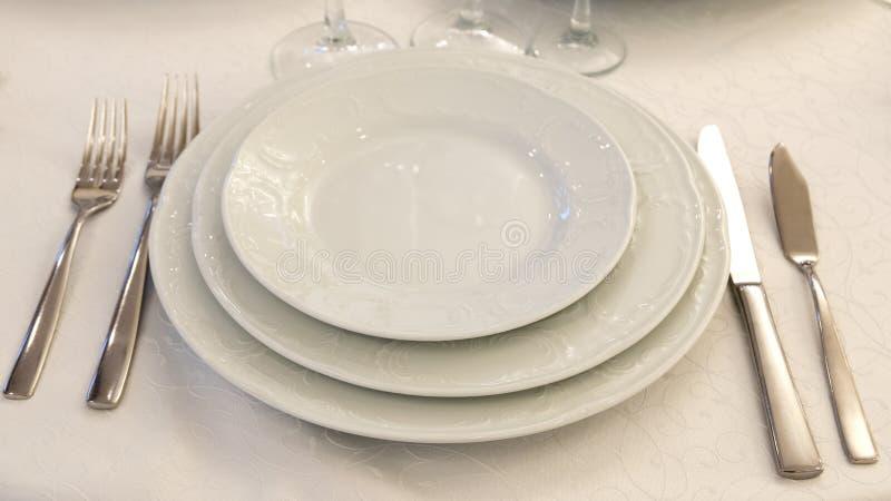 Сервировка стола в ресторане Плиты, вилки и ножи на белой скатерти скопируйте космос стоковое фото rf