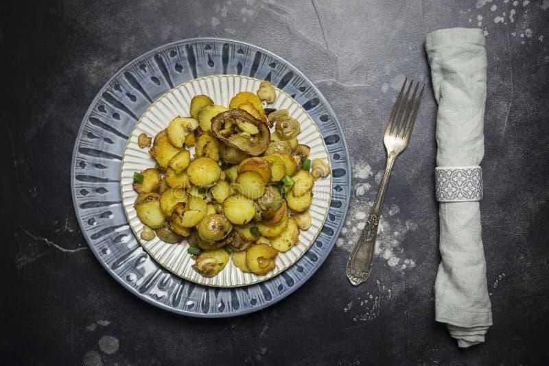 Сервировка стола для обедающего праздника Зажаренные картошки с грибами и луком в белой плите на черной предпосылке Вилка и салфе стоковая фотография rf