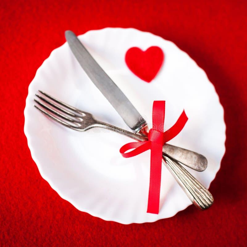 Сервировка стола дня валентинок на красной предпосылке с космосом экземпляра стоковое фото rf