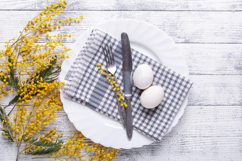 Сервировка стола пасхи Белые яйца, салфетка на плите, цветки мимозы, вилка, нож на деревянном столе стоковое изображение rf