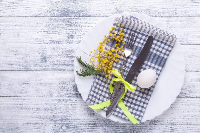 Сервировка стола пасхи Белые яйца, салфетка на плите, цветки мимозы, вилка, нож на деревянном столе стоковая фотография rf