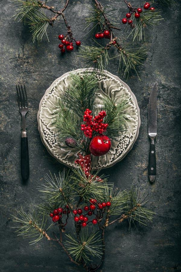 Сервировка стола рождества для традиционного обедающего праздника с плитой, столовым прибором, ветвями ели и ягодами зимы стоковые изображения rf