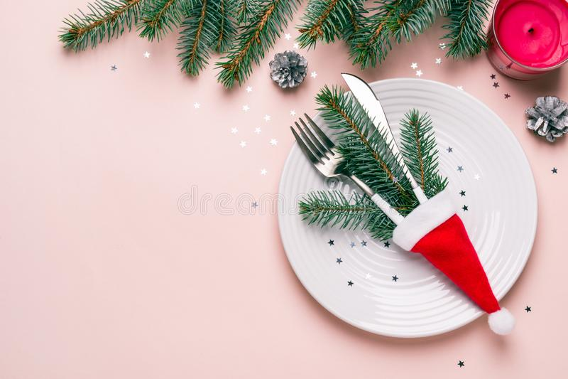 Сервировка стола рождества праздничная Ветви и столовый прибор ели в шляпе Санты на розовой предпосылке стоковые фото