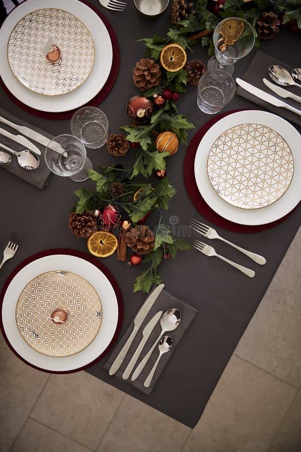 Сервировка стола рождества с безделушками аранжированными на плитах и зеленых и красных украшениях таблицы, надземном взгляде, ве стоковые изображения