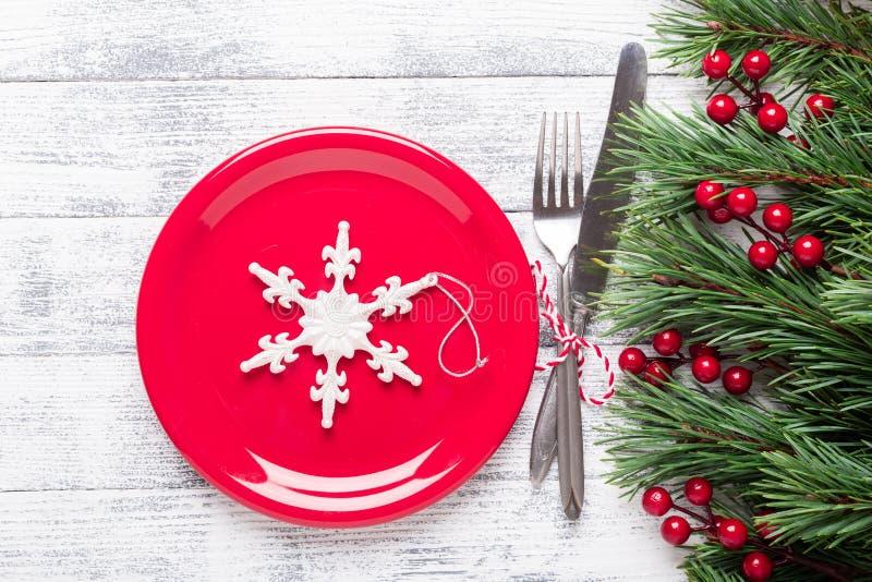 Сервировка стола рождества с красными плитой и silverware на светлой деревянной предпосылке Ветвь ели, ягоды падуба стоковые изображения