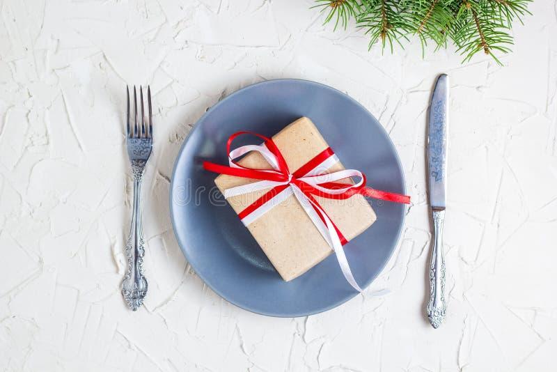 Сервировка стола рождества с серыми плитой, подарочной коробкой и silverware на светлой предпосылке, ветви ели стоковые фотографии rf