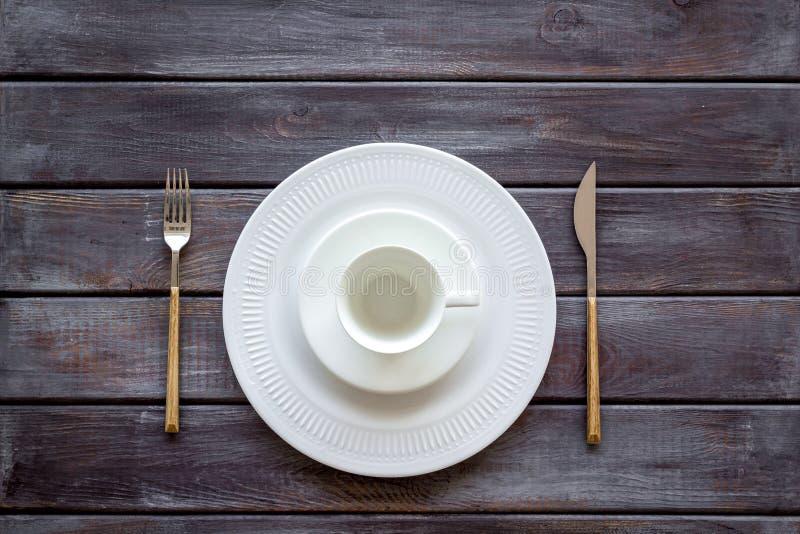 Сервировка стола с плитами и flatware на деревянном взгляде сверху предпосылки стоковые изображения rf