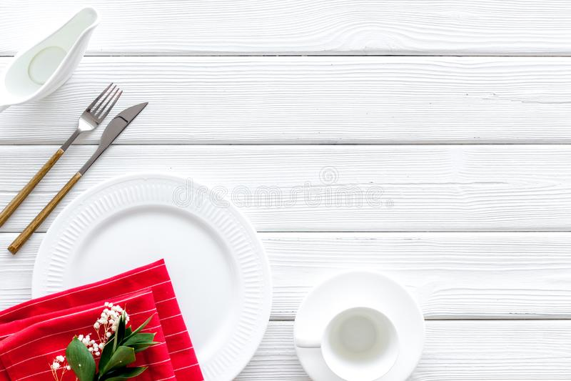 Сервировка стола с плитами, flatware и цветком на белом деревянном космосе экземпляра взгляда сверху предпосылки стоковые фото