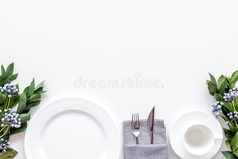 Сервировка стола с плитами, flatware и цветком на белом космосе экземпляра взгляда сверху предпосылки стоковые фотографии rf
