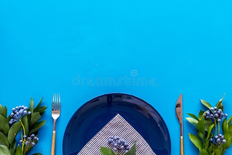 Сервировка стола с плитами, flatware и цветком на голубом космосе экземпляра взгляда сверху предпосылки стоковая фотография