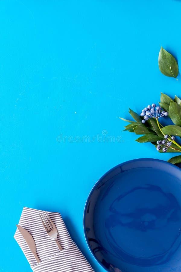 Сервировка стола с плитами, flatware и цветком на голубом космосе экземпляра взгляда сверху предпосылки стоковая фотография rf