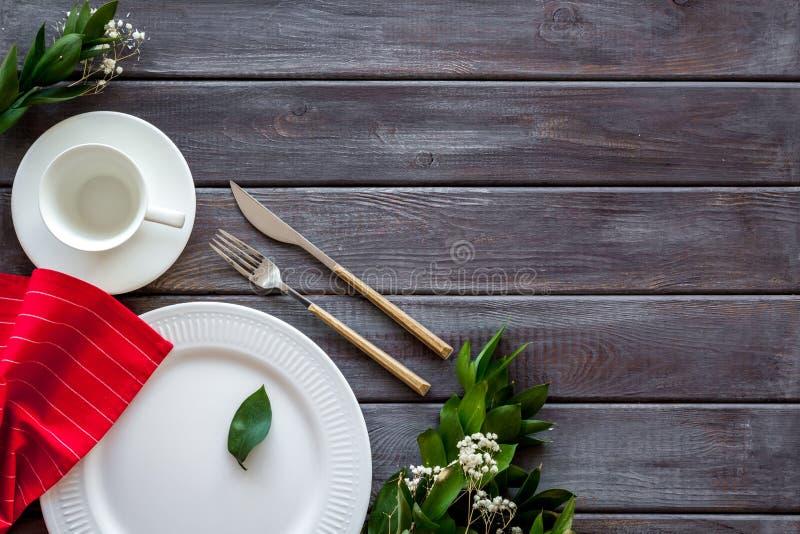 Сервировка стола с плитами, flatware и цветком на деревянном космосе экземпляра взгляда сверху предпосылки стоковое фото rf