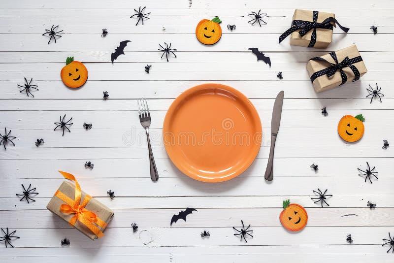 Сервировка стола хеллоуина с столовым прибором, декоративными тыквами, spide стоковая фотография
