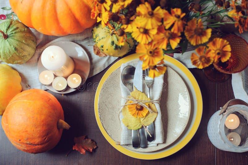 Сервировка стола осени традиционная сезонная дома с тыквами, свечами и цветками стоковые изображения rf