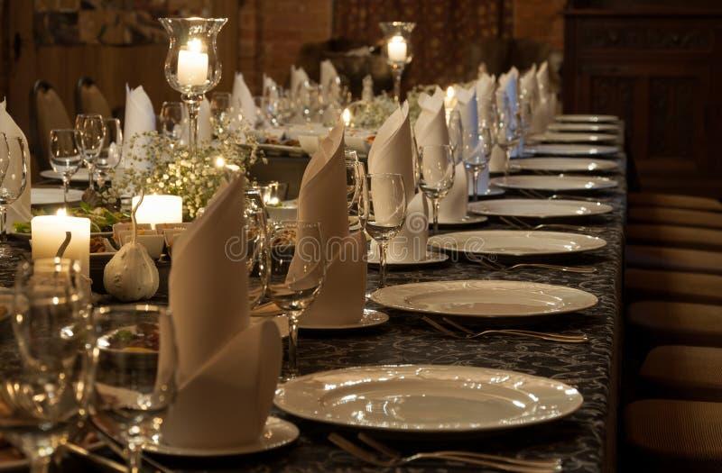 Сервировка стола партии освещенная свечами стоковые изображения