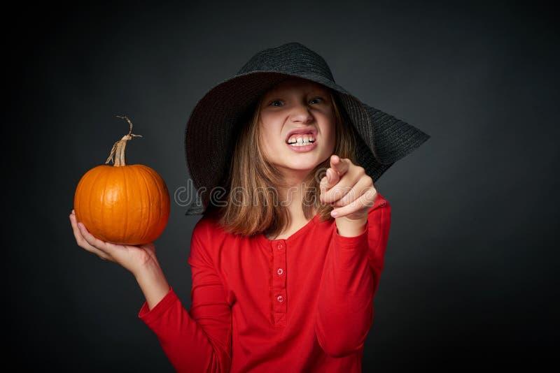 Сердитая девушка в черной шляпе указывая эмоционально на камеру на вас стоковое фото rf