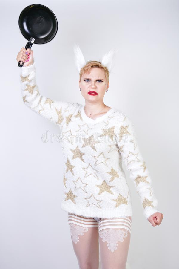 Сердитая девушка с короткими светлыми волосами в пушистом свитере с ушами меха злая добавочная женщина размера с черной пустой ск стоковые фотографии rf