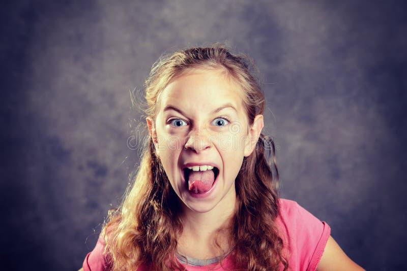 Сердитая девушка с светлыми волосами и розовой рубашкой стоковое фото rf