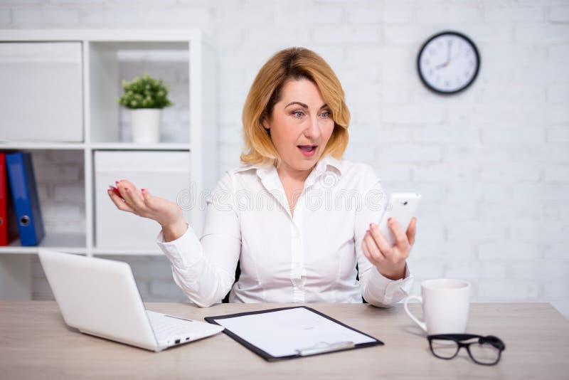 Сердитая зрелая бизнес-леди с умным телефоном в офисе стоковая фотография rf