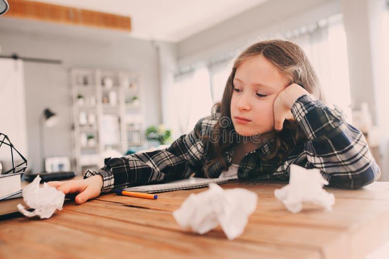 сердитая и утомленная девушка ребенка имея проблемы с домашней работой, бросая бумаги с ошибками стоковая фотография rf
