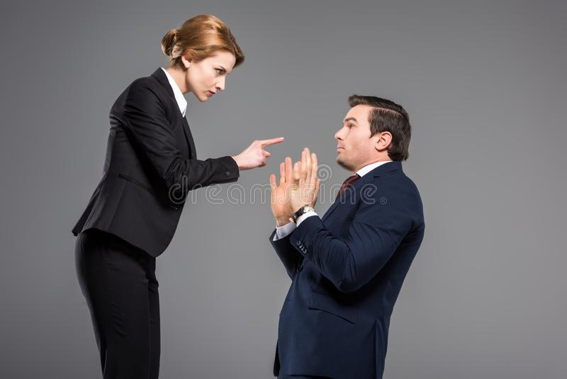 сердитая коммерсантка враждуя и указывая на вспугнутый бизнесмена стоковое изображение rf