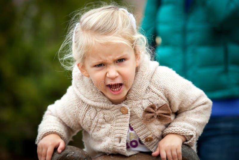 Сердитая маленькая девочка очень рассержена с что-то быть пэ-аш стоковые изображения