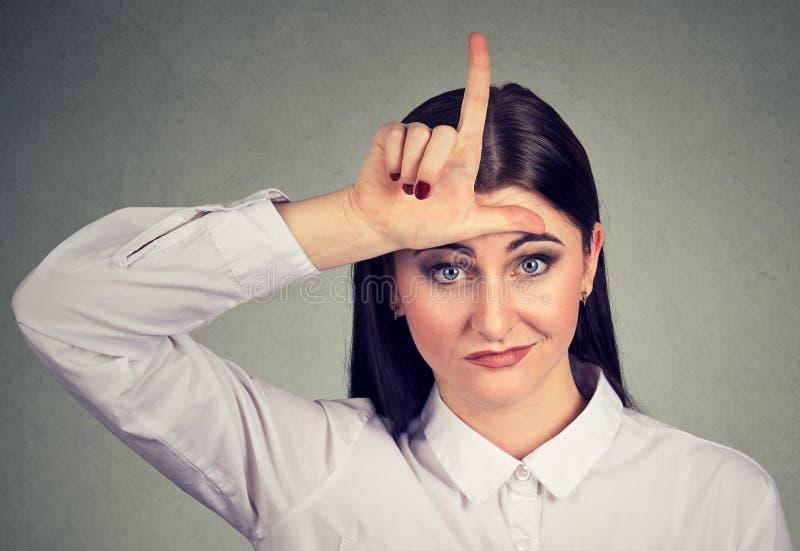 Сердитая молодая женщина показывая знак проигравшего смотря камеру стоковое изображение rf