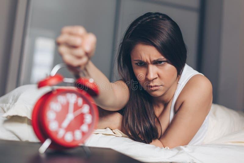 Сердитая молодая женщина убивает будильник кулаком на кровати в утре стоковые фото