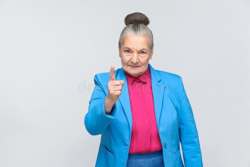 Сердитая постаретая женщина предупреждая вас стоковое фото