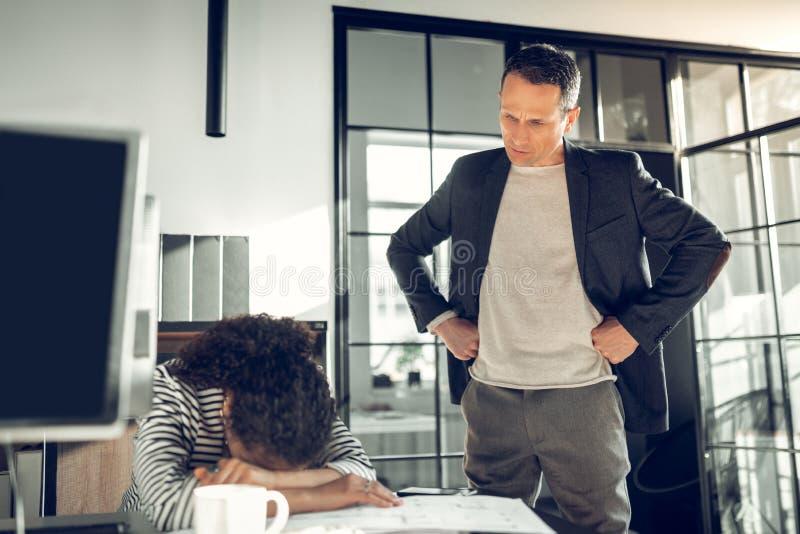 Сердитое положение босса и говорить к его спать секретарши стоковые изображения