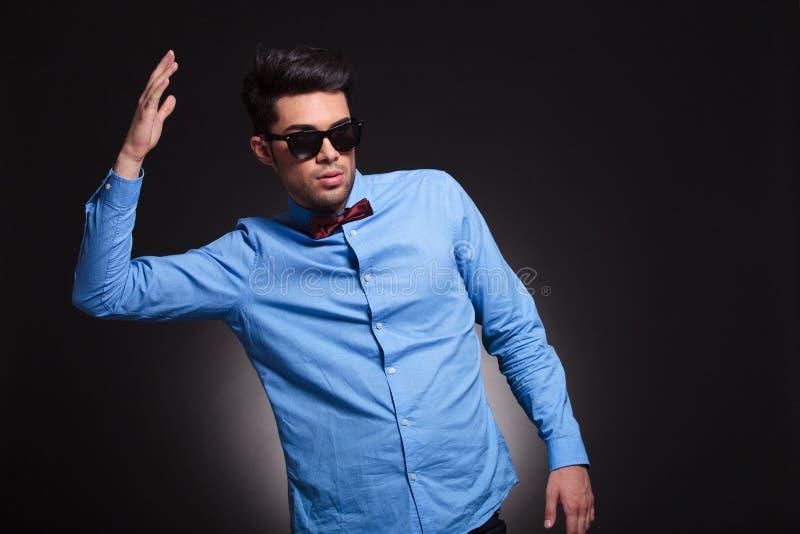 Сердитое положение парня и удержание его руки в воздухе стоковые изображения rf