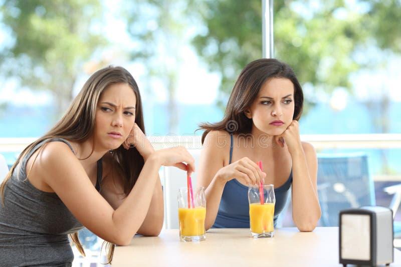 Сердитые друзья игнорируя один другого на каникулах стоковое фото