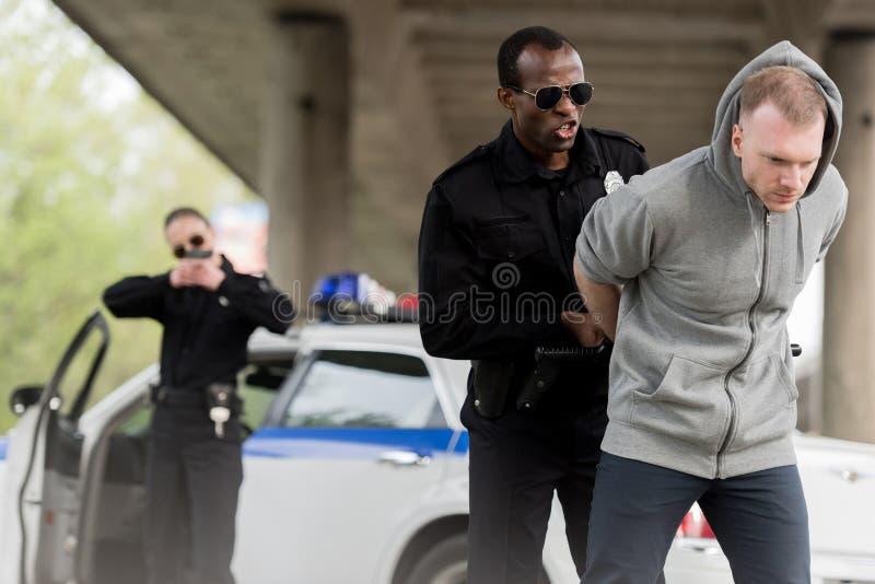 сердитый Афро-американский полицейский арестовывая молодого человека пока женский партнер покрывая его стоковая фотография