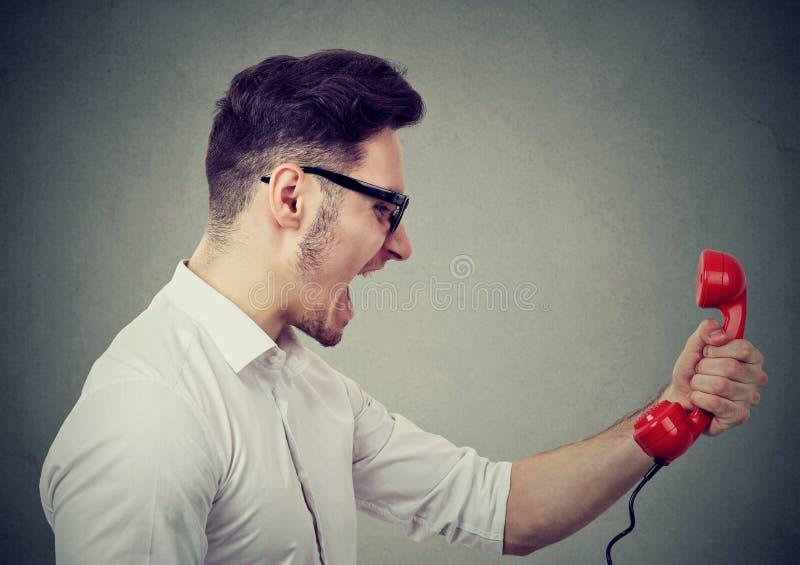 Сердитый бизнесмен выкрикивая на красном телефоне стоковое изображение rf