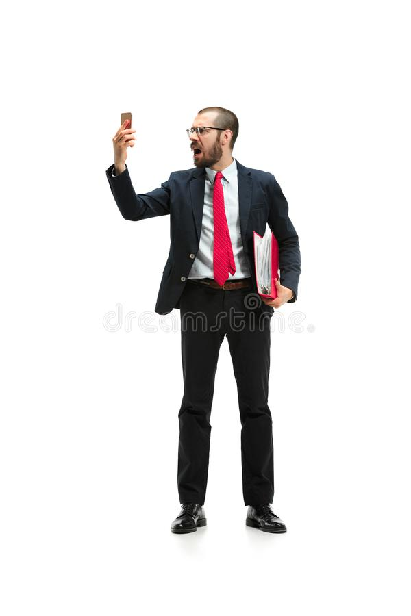 Сердитый бизнесмен говоря на телефоне изолированном над белой предпосылкой в стрельбе студии стоковое фото rf