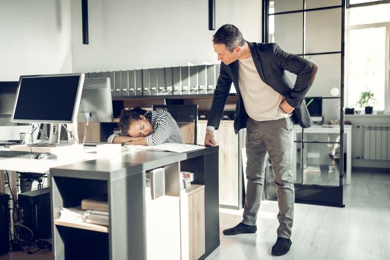 Сердитый босс наблюдая, как его секретарша поспала на рабочем месте стоковые изображения rf