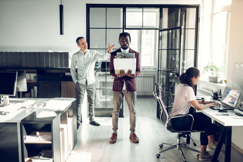 Сердитый босс увольняя темнокожий стажер после ежемесячной работы стоковые изображения