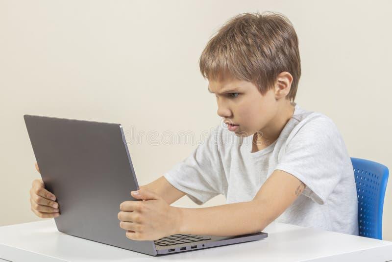 Сердитый грустный мальчик с ноутбуком сидя на таблице стоковая фотография rf