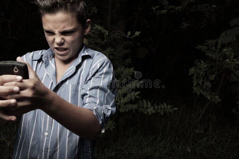 сердитый мобильный телефон мальчика его стоковое фото rf