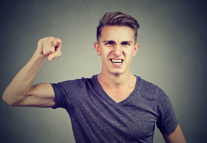 Сердитый молодой человек обвиняя кто-то кричащее стоковое изображение rf