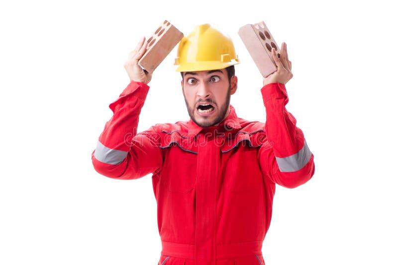 Сердитый построитель ломая кирпичи изолированные на белизне стоковое фото