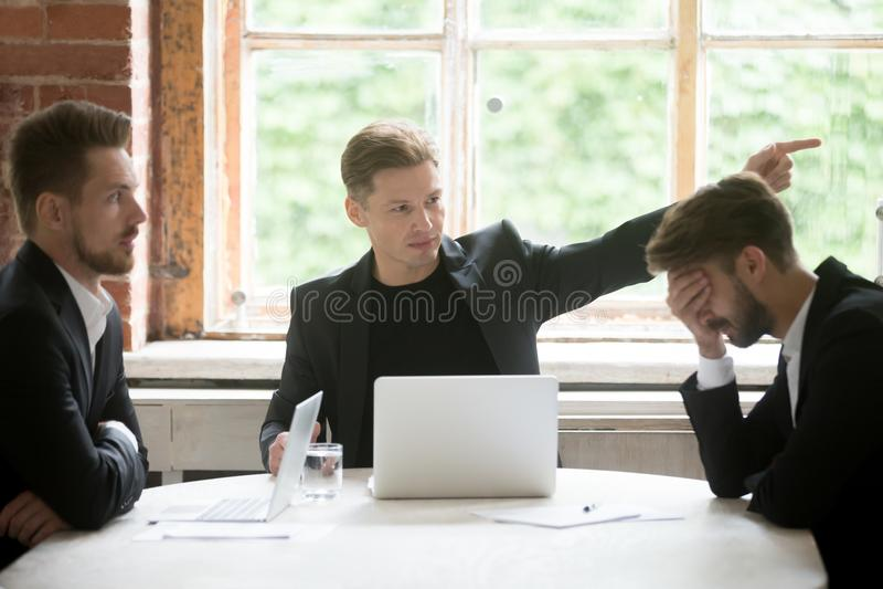 Сердитый работник включения босса с жестом рукой на встрече офиса стоковое изображение rf