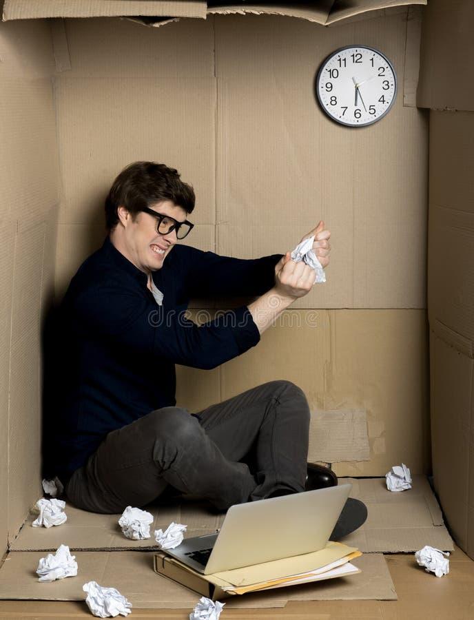 Сердитый работник срывает бумагу внутри малой картонной коробки стоковое фото