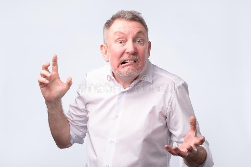 Сердитый старший европейский человек которое угрожает вас стоковое фото rf