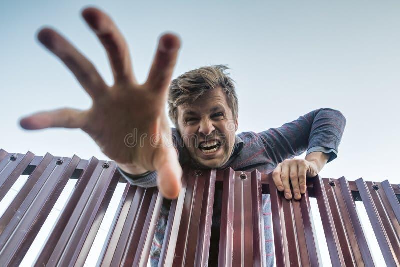 Сердитый человек взбирается злюще над загородкой, ломая границы частной собственности и вытягивая его руку вниз стоковое изображение rf