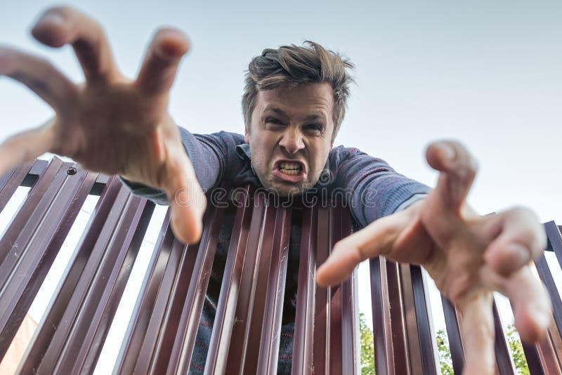 Сердитый человек взбирается злюще над загородкой, ломая границы частной собственности и вытягивая его руку вниз стоковые изображения