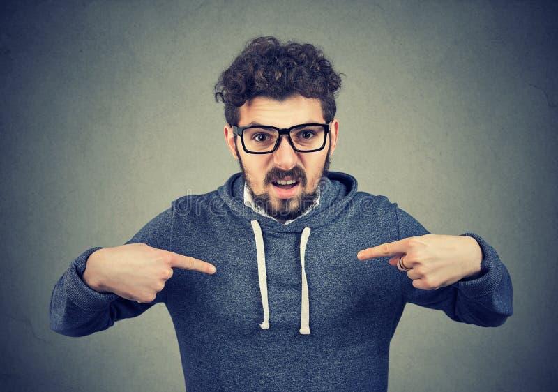 Сердитый человек в eyeglasses слишком остро реагируя пока указывающ на себя стоковое изображение