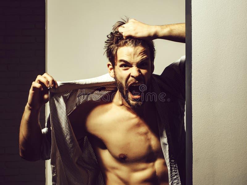 Сердитый человек показывает торс мышцы стоковые фото